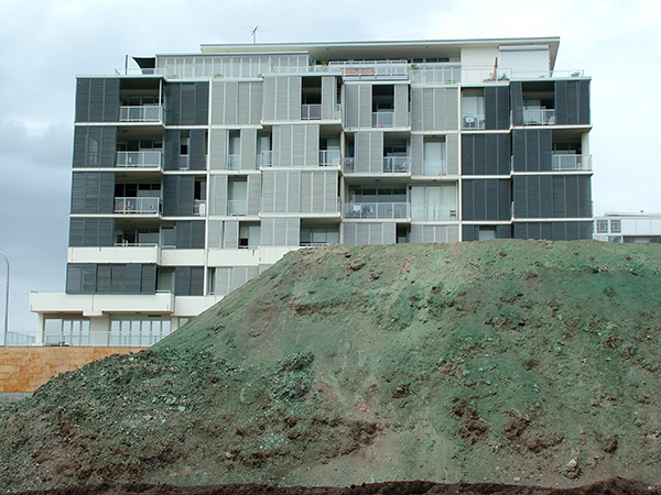 A large pile of dirt is sitting in front of a residential apartment building.